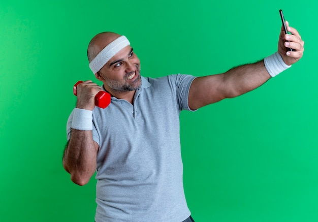 Dojrzały sportowy mężczyzna w opasce z ręcznikiem na szyi, podnosząc rękę z hantlami, biorąc selfie za pomocą swojego smartfona uśmiechając się stojąc nad zieloną ścianą