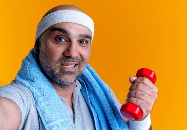 Dojrzały sportowy mężczyzna w opasce z ręcznikiem na szyi, trzymając hantle patrząc do przodu z uśmiechem na twarzy stojącej nad pomarańczową ścianą
