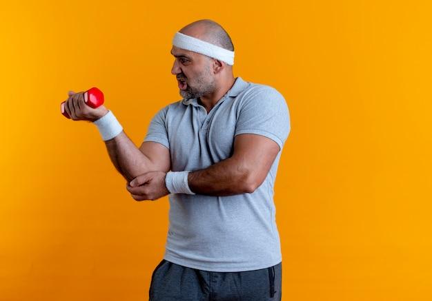 Dojrzały sportowy mężczyzna w pałąku na głowę, ćwicząc z hantlami, patrząc zmęczony i wyczerpany stojąc nad pomarańczową ścianą