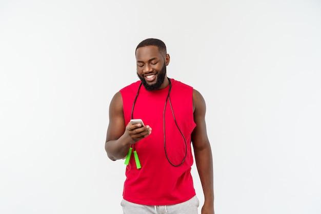 Dojrzały sprawny człowiek afroamerykanów sms-y na telefon komórkowy i trzymając elastyczną linę.