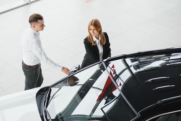 Dojrzały sprzedawca pokazuje nowy samochód parze w salonie