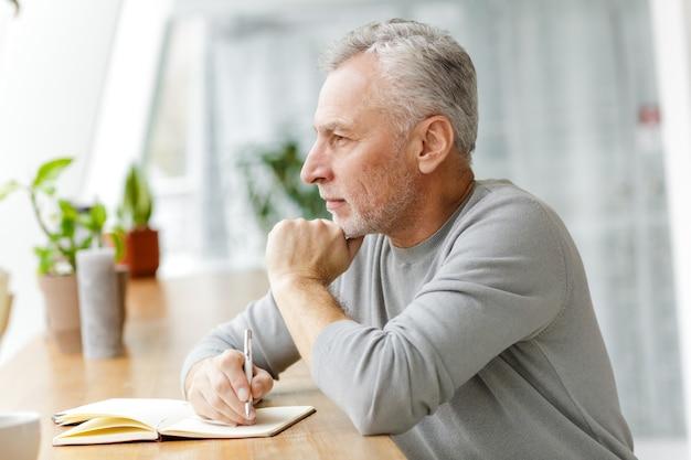 Dojrzały, starszy biznesmen siedzieć w kawiarni, pisząc notatki w notesie.
