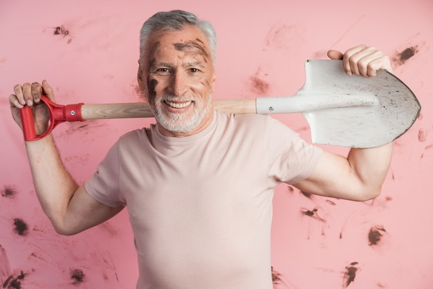 Dojrzały, starszy mężczyzna z łopatą na ramionach na brudnej różowej ścianie