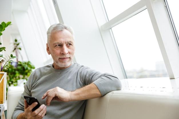 Dojrzały starszy siwy biznesmen brodaty siedzieć w kawiarni przy użyciu telefonu komórkowego patrząc na bok.