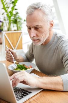 Dojrzały starszy siwy biznesmen brodaty siedzieć w kawiarni zjeść obiad przy użyciu komputera przenośnego.