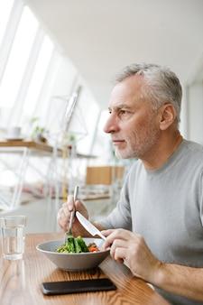 Dojrzały starszy siwy biznesmen brodaty siedzieć w kawiarni zjeść obiad.