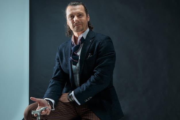 Dojrzały stylowy mężczyzna w garniturze na szarym tle studio. biznesmen siedzi na fotelu