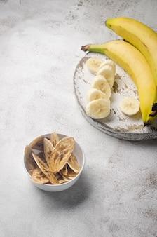 Dojrzały surowy banan i suszone plasterki bananów w płytce na jasnoszarym tle. chipsy owocowe. koncepcja zdrowego odżywiania, przekąska, bez cukru. widok z góry, kopia przestrzeń.