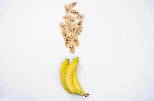 Dojrzały surowy banan i suszone plasterki bananów żetony rozrzucone na białym tle. chipsy owocowe.