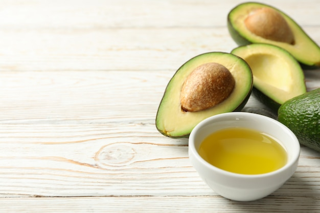 Dojrzały świeży avocado i olej na białym drewnianym stole, zamykają up