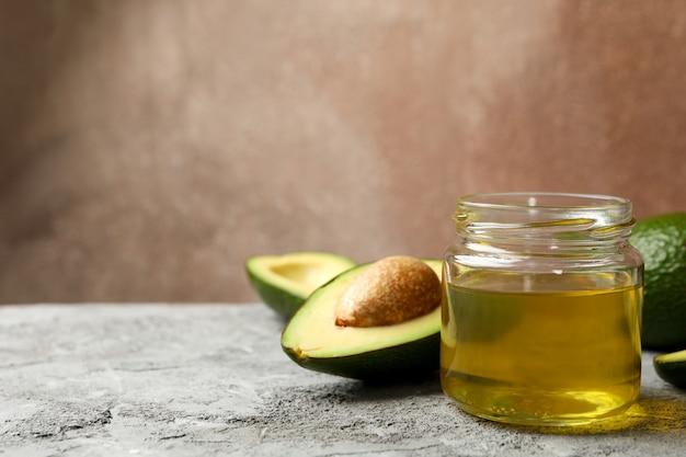 Dojrzały świeży avocado i olej na popielatym stole, zamykamy up
