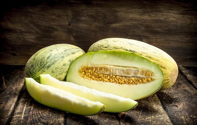 Dojrzały świeży melon na drewnianym tle