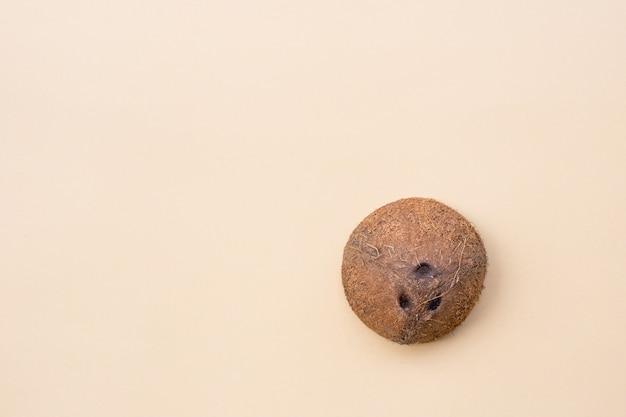 Dojrzały, świeży, słodki, zdrowy, smaczny kokos na pastelowym beżowym tle. mieszkanie świeckich, widok z góry, koncepcja żywności