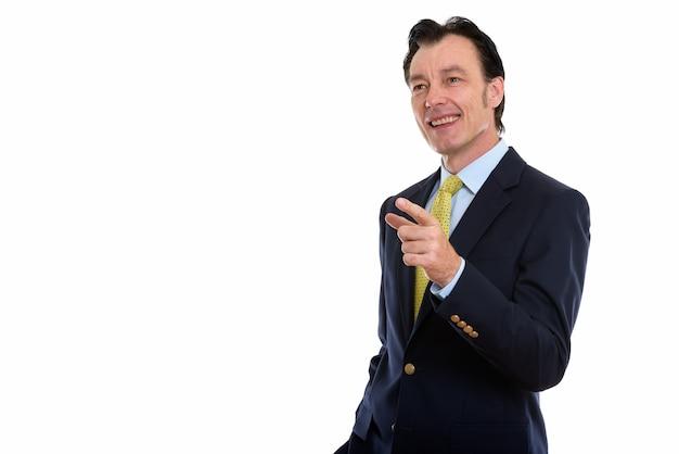 Dojrzały szczęśliwy biznesmen uśmiechnięty, wskazując palcem