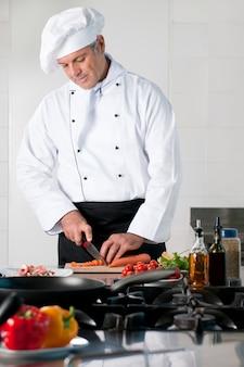 Dojrzały szef kuchni tnie marchewkę w kuchni restauracji