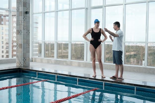 Dojrzały trener ze stoperem wskazującym na pas ruchu, dając zadanie pływaczce