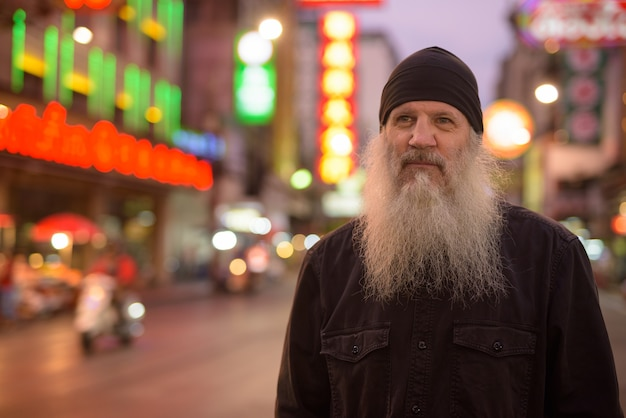 Dojrzały turysta mężczyzna z długą brodą myśli w chinatown nocą