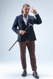 Dojrzały, ubrany mężczyzna w garniturze trzymającym laskę.