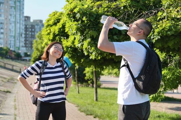 Dojrzały uśmiechnięty mężczyzna i kobieta w odzieży sportowej z plecakami i matą do ćwiczeń, spacerujący po parku miejskim, rozmawiając i pijąc wodę z butelki