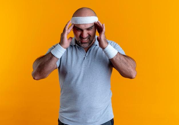 Dojrzały wysportowany mężczyzna w opasce dotyka skroni, cierpiący na silny ból głowy, stojący nad pomarańczową ścianą