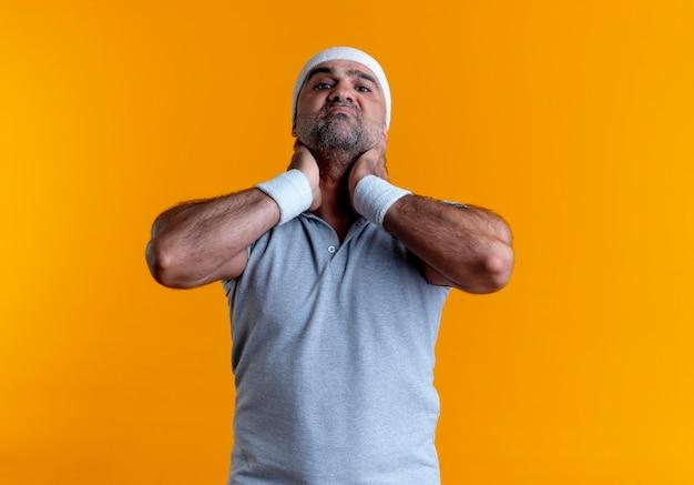 Dojrzały wysportowany mężczyzna w opasce patrzy do przodu niezadowolony dotykając szyi, czując dyskomfort stojąc nad pomarańczową ścianą
