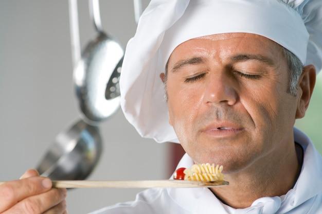 Dojrzały, zadowolony szef kuchni czuje zapach swojego jedzenia podczas gotowania w restauracji