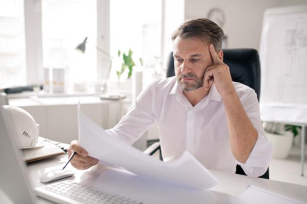 Dojrzały zamyślony inżynier patrząc na szkic, myśląc o pomysłach lub sprawdzając go na stanowisku pracy w biurze