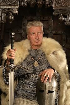 Dojrzały zamyślony średniowieczny rycerz na tronie