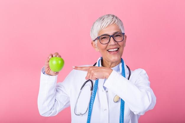 Dojrzały żeński dietetyk trzyma jabłka