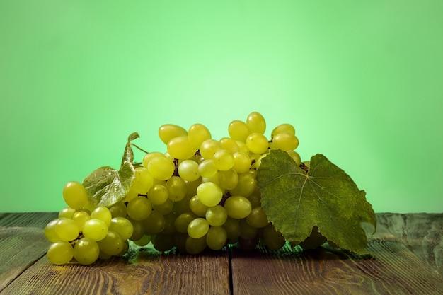 Dojrzały zielony winogrono i na drewnianym stole na zielonym tle.