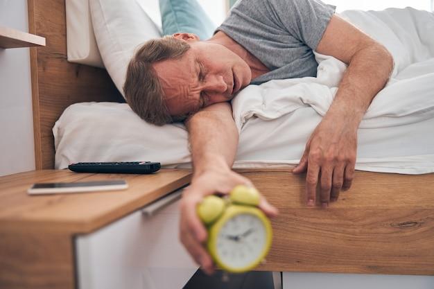 Dojrzały zmęczony mężczyzna kładzie głowę na ramieniu i ogląda w domu sny o wakacjach