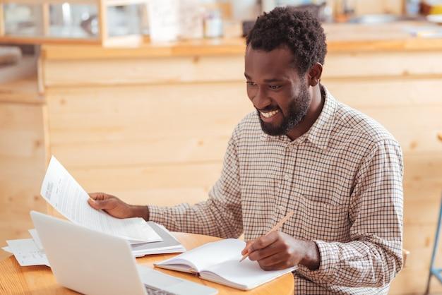 Dokładna analiza. przyjemny, optymistyczny młody człowiek, siedzący przy stoliku w kawiarni i analizujący dane z wydruków, uśmiechając się radośnie