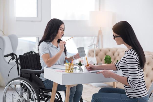 Dokładna prognoza. inteligentna niepełnosprawna kobieta i koleżanka pracująca razem przy użyciu ołówków