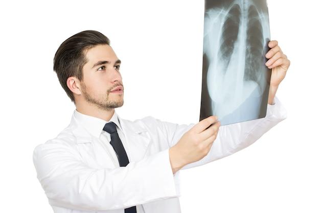 Dokładne badanie. portret studyjny połowy długości mężczyzny lekarza badającego prześwietlenie pacjenta