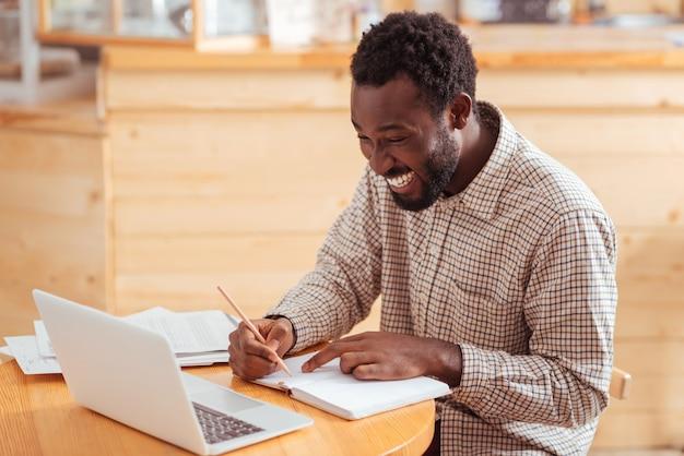 Dokładne planowanie. przystojny radosny mężczyzna siedzi przy stole w kawiarni i planuje swój dzienny harmonogram w zeszycie, uśmiechając się radośnie