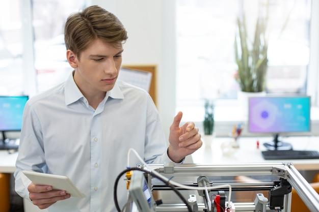 Dokładny uczeń. przyjemny młody człowiek badający mechanizm drukarki 3d, porównując swoje obserwacje z instrukcją na tablecie