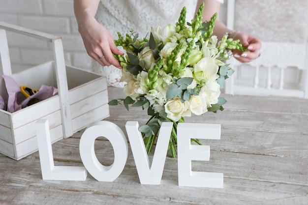 Dokonywanie bukiet ślubny w warsztacie florystycznym. nie do poznania kwiaciarnia składa delikatny bukiet z białych róż, świeżego wawrzynu i polnych kwiatów. wystrój lub piękny prezent dla uroczej kobiety.
