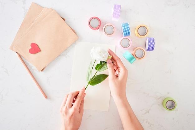 Dokonywanie dekoracji lub kartki z życzeniami. paski papieru, kwiat, nożyczki