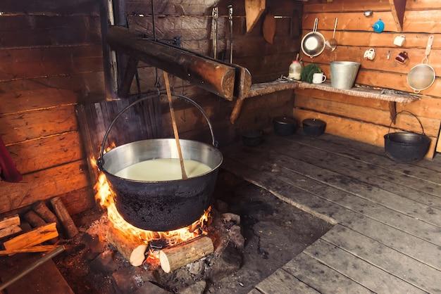 Dokonywanie ekologicznego sera w drewnianym górskim domu. ludzie mieszkają tu latem, doją krowy, które są na pastwisku, gotują ser na otwartym ogniu. uchwycony 15 listopada 2015 r. w karpatach/ukraina