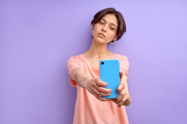 Dokonywanie selfie modelki na telefon komórkowy, blogowanie. przystojna kobieta z krótkimi włosami patrzy w kamerę telefonu i pozuje, ubrana w swobodny strój. nowoczesne technologie.skup się na smartfonie