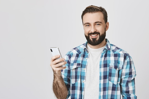 Dokonywanie telefonu przystojny uśmiechnięty brodaty mężczyzna