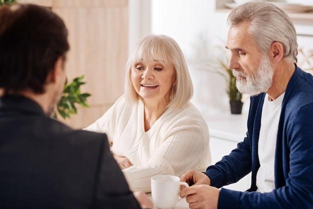 Dokonywanie zakupu nieruchomości. optymistyczna szczęśliwa para starszych siedzi w domu i rozmawia z doradcą, wyrażając zainteresowanie