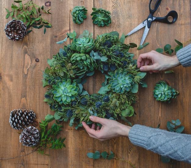 Dokonywanie zielony świąteczny wieniec z sukulentami.