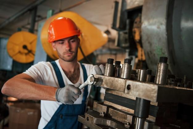 Dokręca detale maszyny kluczem. mężczyzna w mundurze pracuje nad produkcją. nowoczesna technologia przemysłowa.
