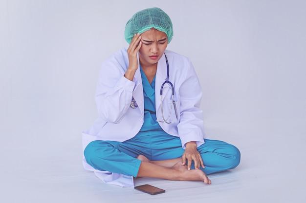 Doktor bóle głowy od ciężkiej pracy i stresujące na białym tle.