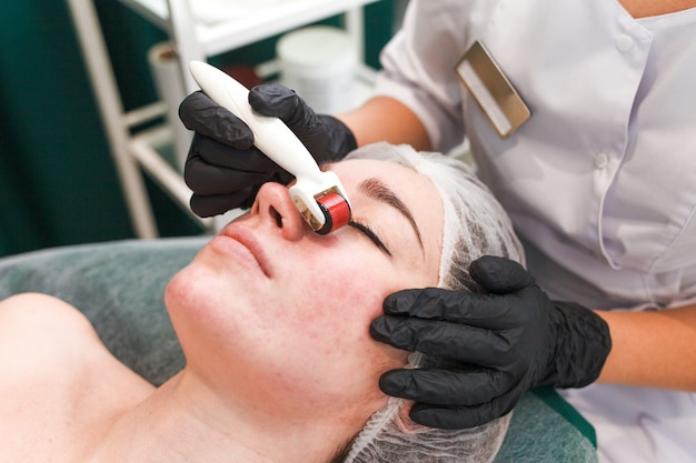 Doktor kosmetolog wykonuje masaż twarzy za pomocą wałka dermo