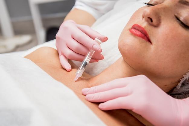 Doktor kosmetolog wykonuje procedurę zastrzyków dekoltu. młoda kobieta w salonie piękności.