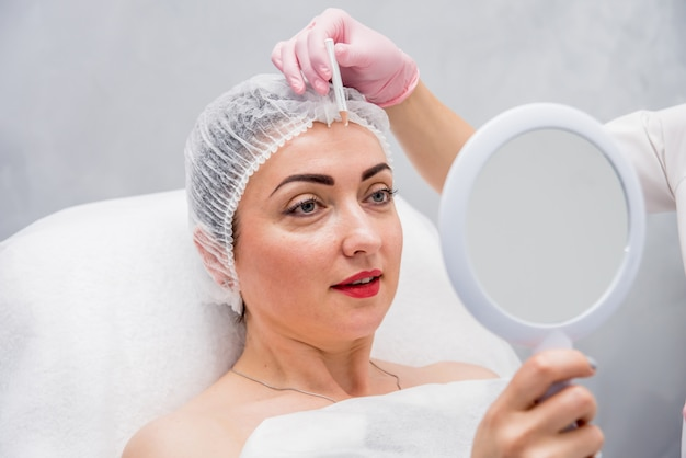 Doktor kosmetolog wykonuje procedurę zastrzyków twarzy. młoda kobieta w salonie piękności.