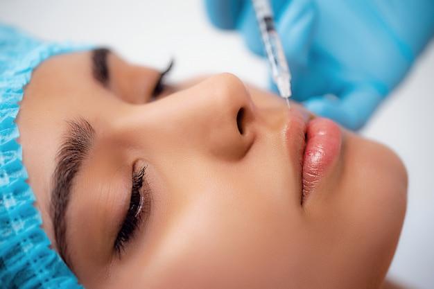 Doktor kosmetolog wykonuje zabieg odmładzania zastrzyków twarzy w celu napinania i wygładzania zmarszczek na skórze twarzy kobiety w salonie piękności. kosmetyki do pielęgnacji skóry