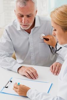 Doktor pisania w schowku podczas osłuchiwania